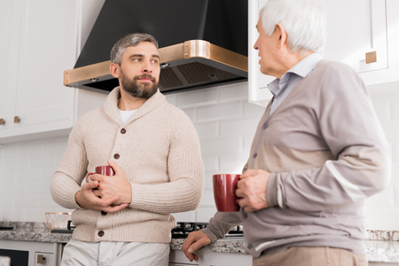 Men Chatting in Kitchen Imagens