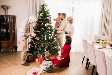 Big Family Decorating Christmas Tree at Home