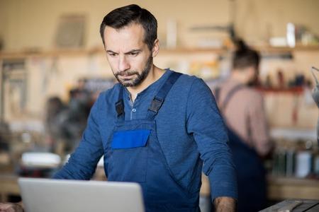 Mature Worker Using Laptop Фото со стока
