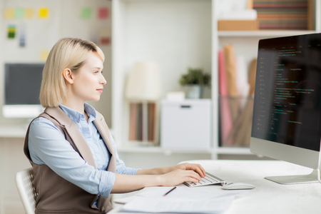 Busy lady composing code for software app