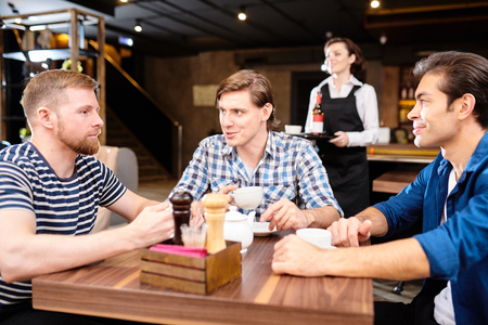 Content young friends chatting over tea in cafe Stockfoto