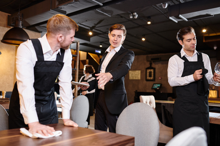Restaurant manager giving task to waiter during cleanup Archivio Fotografico - 113918029