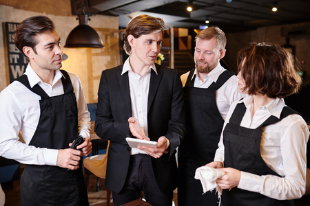Manager assessing work of waiters Stock Photo