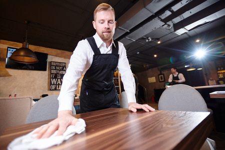Handsome young waiter cleaning table in restaurant