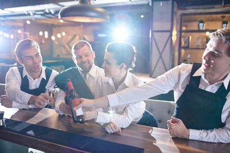 Group of waiters celebrating success after hours in restaurant