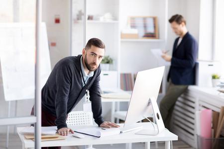 Bearded Businessman Standing at Desk