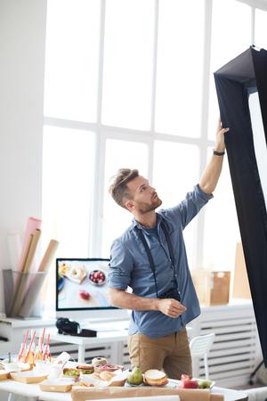Photographer Adjusting Light Equipment in Studio