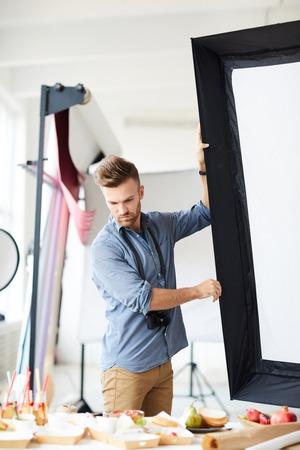 Photographer Adjusting Lights in Studio