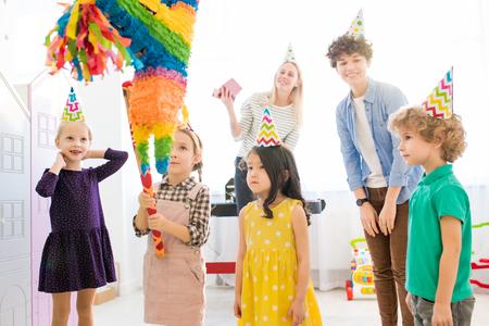 Girl striking pinata at birthday party Stock Photo