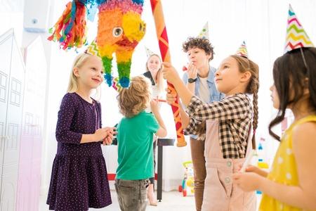 Confident girl hitting colorful pinata at kids celebration