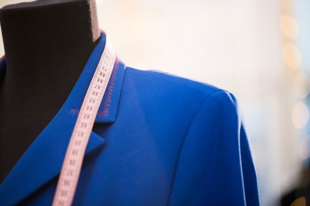 Close up of classic jacket in electric blue color shown on mannequin in atelier studio, copy space