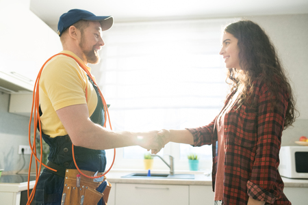 Smiling lady thanking repairman for work