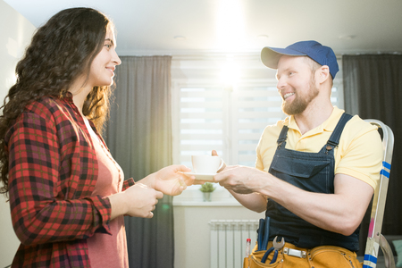 Hospitable lady giving coffee to repairman