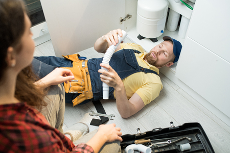 Young plumber changing trap under sink Stock Photo