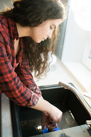 Woman clearing clogged drains with plunger