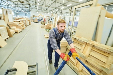 Handsome young worker pushing pallet jack over factory warehouse