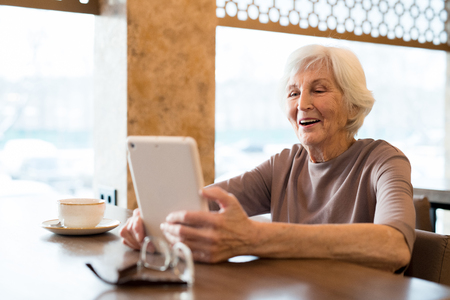 Cheerful excited elderly woman enjoying reading in cafe