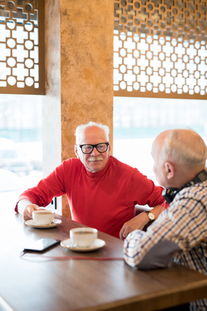 Curious senior man talking to friend in cafe