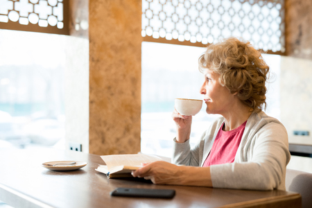 Pensive retired woman drinking coffee in cafe