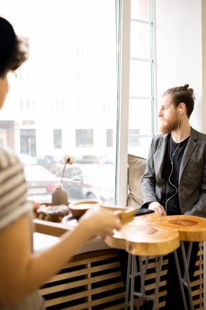 Pensive hipster man looking out window in cafe