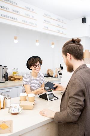 Chico hipster pagando café con smartphone