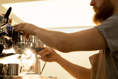 Barista man attaching portafilter to espresso machine