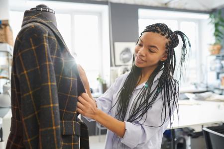 Designer sewing jacket in workshop