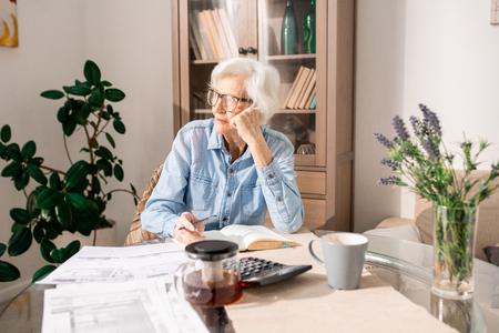 Mujer Senior pensativa contando impuestos Foto de archivo