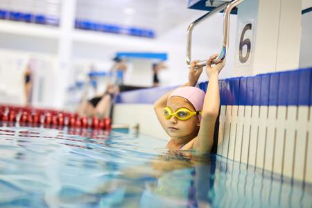 Little girl exercising in pool