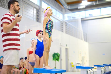 Athletes with coach training in pool