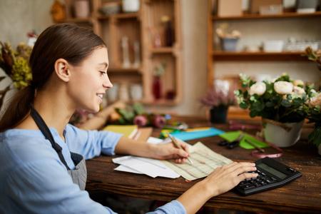 Mujer haciendo contabilidad en tienda Foto de archivo