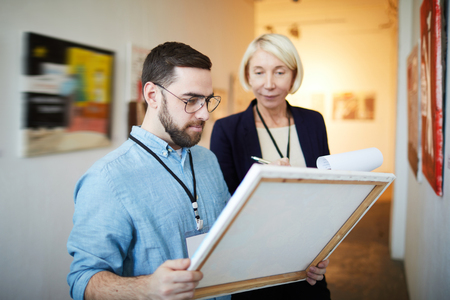 Workers Appraising Pictures Stock Photo