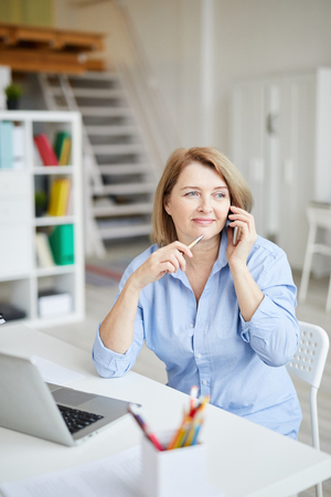 Mature Businesswoman Talking by Phone 스톡 콘텐츠