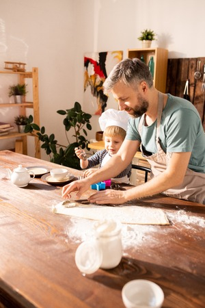 Father and son cutting shapes from dough Standard-Bild
