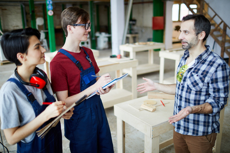 Carpenter sharing knowledge with young students Stock Photo