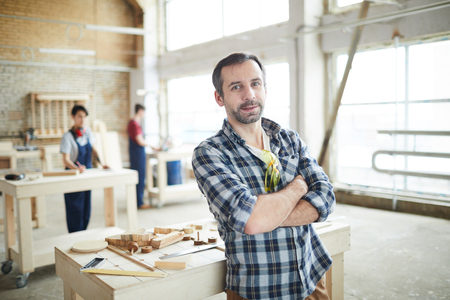 Confident workman in carpentry shop