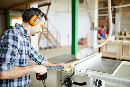 Adjusting wooden plank on workbench