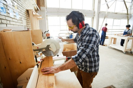 Concentrated man cutting wooden piece Standard-Bild