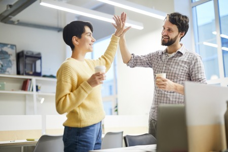 Excited colleagues giving high five Stock Photo