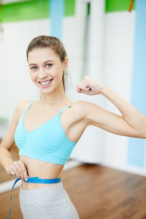 Woman Measuring Waist in Gym