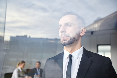 Serious man by window Stock Photo