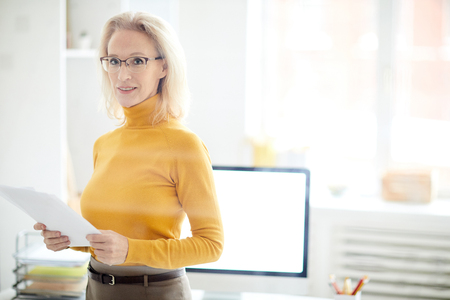 Mature Businesswoman Standing Behind Glass