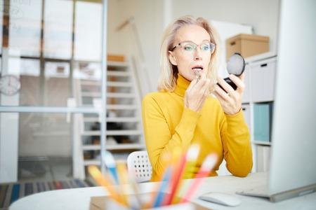 Mature Woman Doing Makeup at Work