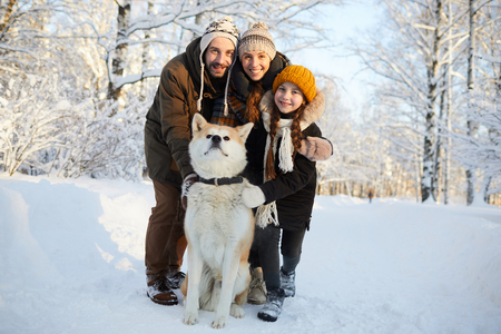 Family Posing with Dog Outdoors Stock Photo - 117092980