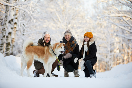 Happy Family Enjoying Walk with Dog