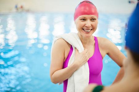 Fröhliche ältere Frau am Pool Standard-Bild