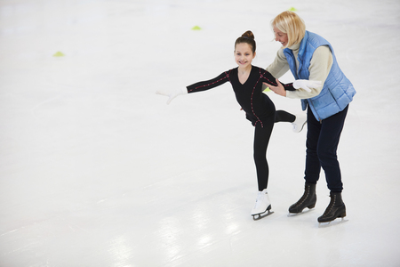 Coach Helping Girl Figure Skating Banco de Imagens
