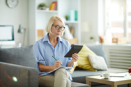 Woman Calculating Budget at Home Imagens