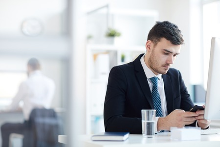 Man texting by workplace