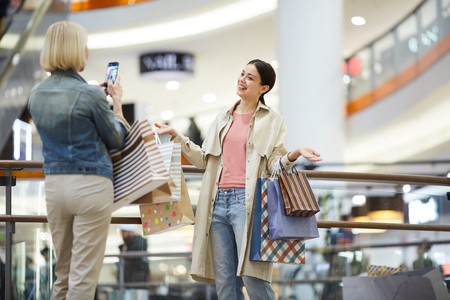 Lady photographing friend with plenty shopping bags Stock Photo